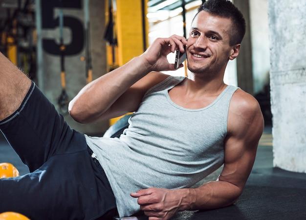 Feliz, muscular, homem fala, ligado, cellphone, em, ginásio