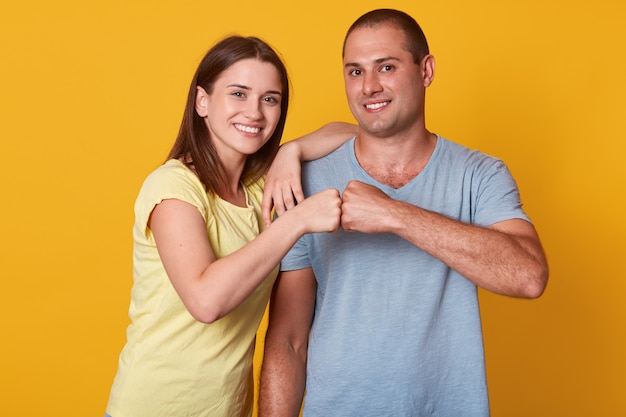 Feliz namorada encantada, sorrindo, colocando uma mão no ombro do namorado, tendo os punhos juntos, apaixonado por trabalho em equipe, homem positivo de pé em linha reta. conceito de relacionamento.