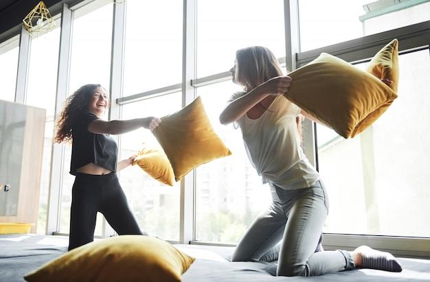 Feliz namoradas felizes estão lutando com almofadas.