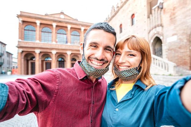 Feliz namorado e namorada apaixonada tomando selfie com máscaras no tour pela cidade velha