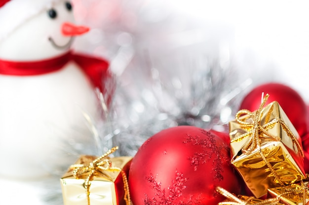 Feliz natal, ano novo, boneco de neve, presentes em caixas douradas e bolas vermelhas em um fundo azul e branco bokeh.