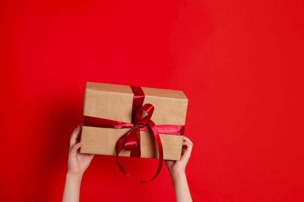 Feliz natal. as mãos das crianças seguram uma caixa de presente amarrada com uma fita vermelha em um fundo vermelho. um lugar para texto. foto de alta qualidade