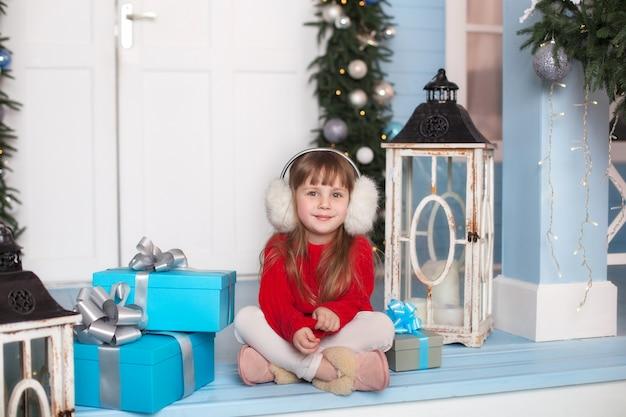 Feliz natal! bonitinha está sentada na camisola vermelha com presente na varanda da casa. criança senta-se em uma varanda decorada para o natal. criança abre um presente de natal.
