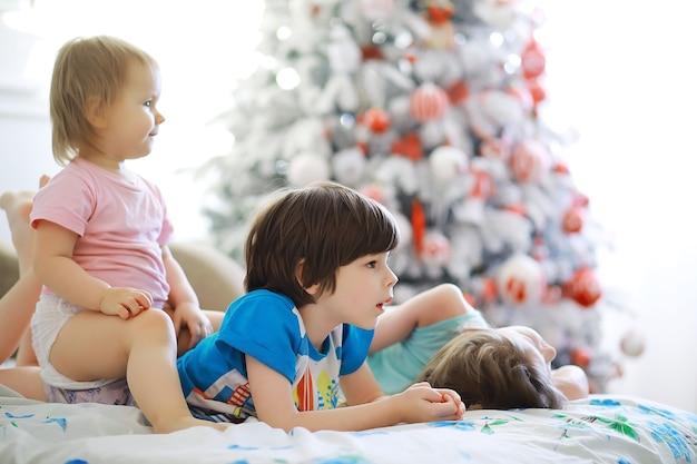 Feliz natal brilhante. bebê adorável, aproveite o natal. memórias de infância. santa menina criança comemorar o natal em casa. feriado familiar. menina bonita criança alegre humor brincar perto de árvore de natal.