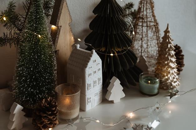 Feliz natal. casinha de cerâmica de natal, pinheiros de madeira. decorações festivas e modernas.