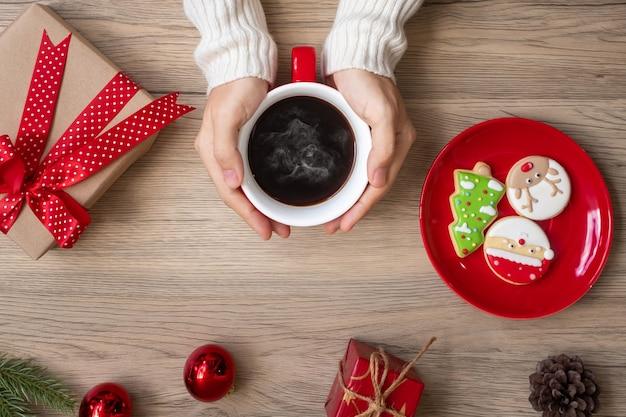 Feliz natal com a mão de uma mulher segurando a xícara de café e o biscoito caseiro na mesa. conceito de véspera de natal, festa, feriado e feliz ano novo