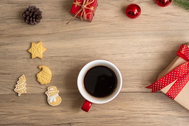 Feliz natal com biscoitos caseiros e xícara de café no fundo da mesa de madeira. conceito de véspera de natal, festa, feriado e feliz ano novo