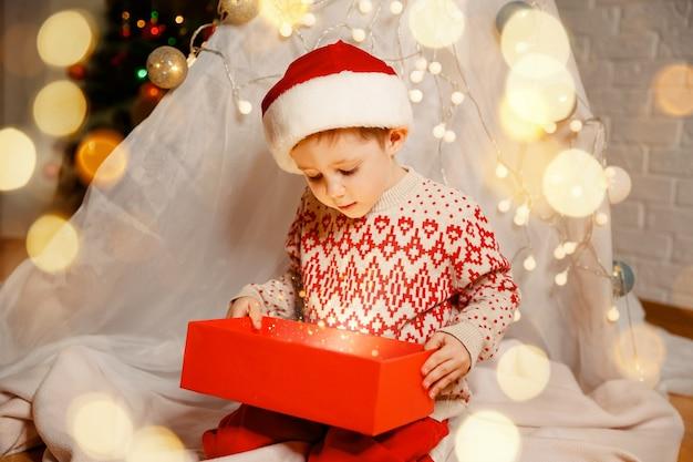 Feliz natal criança feliz com presente mágico perto da árvore de natal