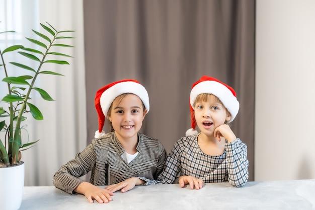Feliz natal, crianças engraçadas, irmãs gêmeas com chapéus de papai noel