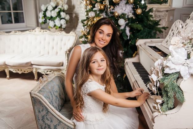 Feliz natal e boas festas. a mãe alegre e sua filha bonita no interior clássico branco, tocando em um piano branco decoraram a árvore de natal. ano novo