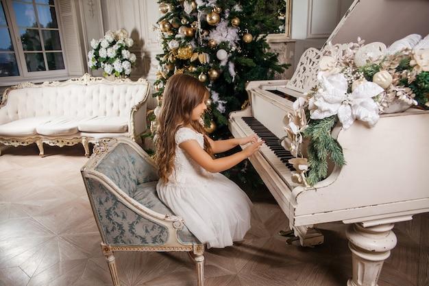 Feliz natal e boas festas. a menina bonito no interior clássico branco que joga em um piano branco decorou a árvore de natal. ano novo
