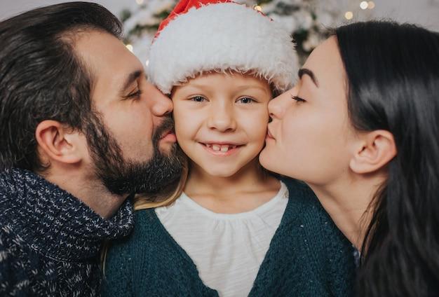 Feliz natal e boas festas alegre mãe, pai beijando a filha.