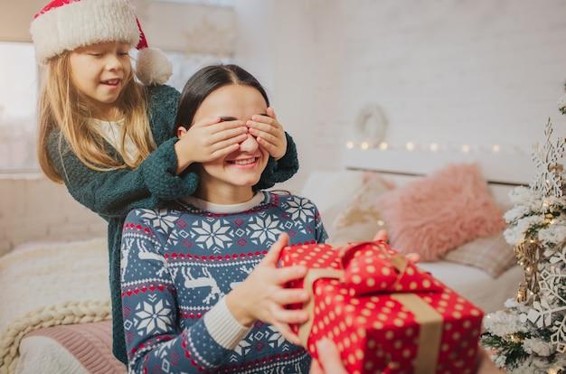 Feliz natal e boas festas alegre mãe, pai e sua linda filha trocando presentes.