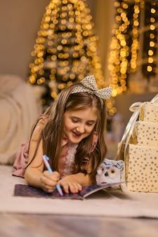 Feliz natal e boas festas. criança menina bonitinha escreve a carta para o papai noel perto da árvore de natal dentro de casa.
