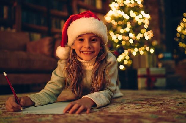 Feliz natal e boas festas! criança menina bonitinha escreve a carta para o papai noel perto da árvore de natal dentro de casa.