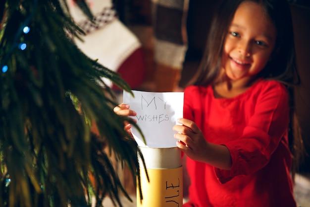 Feliz natal e boas festas. criança menina bonitinha escreve a carta para o papai noel perto da árvore de natal em casa interior. feriado, infância, inverno, conceito de celebração