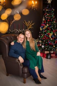 Feliz natal e boas festas. família, pai e filha no fundo de uma árvore de natal.