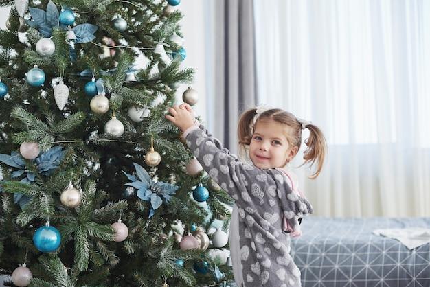 Feliz natal e boas festas! jovem, ajudando a decorar a árvore de natal, segurando alguns enfeites de natal na mão
