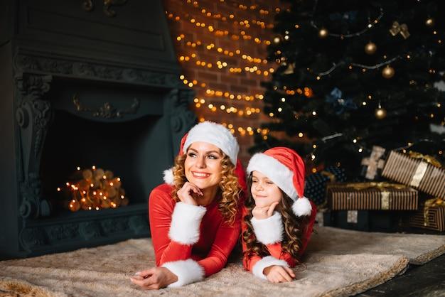 Feliz natal e boas festas! linda mãe com filha em fantasias de natal, passam algum tempo juntos perto da árvore de natal.