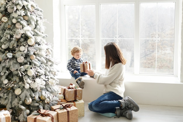 Feliz natal e boas festas! mãe alegre e bonito menino trocando presentes. pai e filho se divertindo perto de árvore de natal dentro de casa. família amorosa com presentes no quarto.