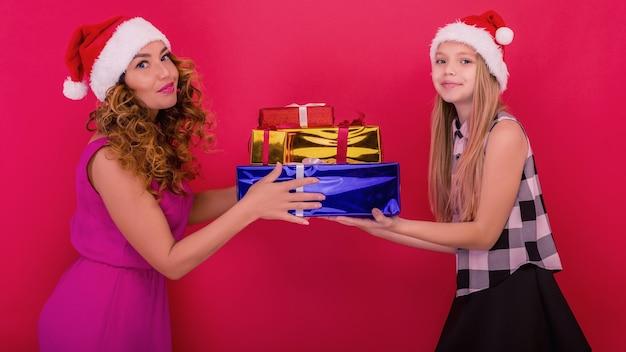 Feliz natal e boas festas. mãe alegre e sua linda filha segurando um presente de natal
