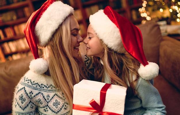 Feliz natal e boas festas! mãe alegre e sua linda filha trocando presentes. pai e filho se divertindo perto da árvore dentro de casa. família amorosa com presentes na sala.