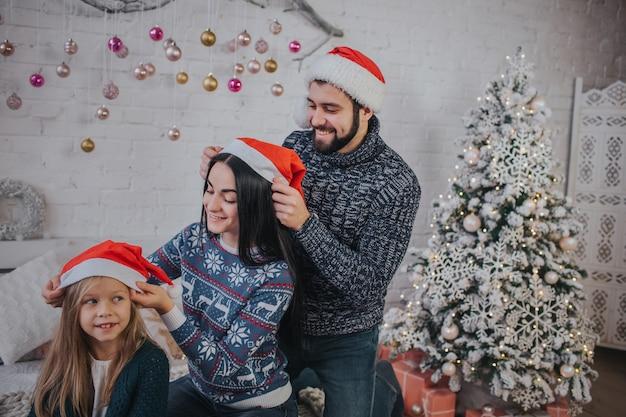 Feliz natal e boas festas mãe alegre, pai e sua filha se vestem com chapéus de natal um do outro. pai e filho se divertindo perto de árvore de natal dentro de casa. manhã de natal.