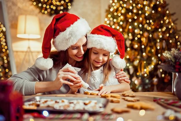 Feliz natal e boas festas. mãe e filha cozinhando biscoitos de natal.