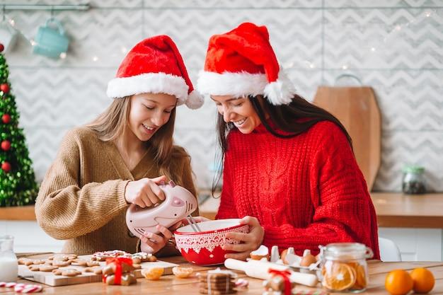 Feliz natal e boas festas. mãe e filha cozinhando biscoitos em casa para as férias de natal