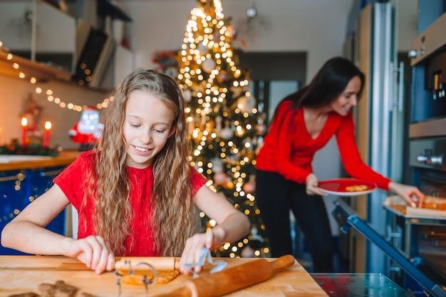 Feliz natal e boas festas. mãe e filhas cozinhando biscoitos de natal
