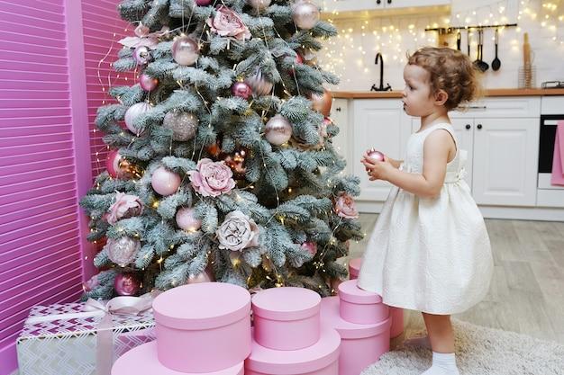 Feliz natal e boas festas, menina bonitinha está decorando a árvore de natal dentro de casa.