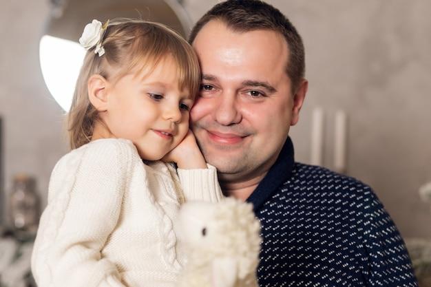 Feliz natal e boas festas. pai alegre, abraçando a filha bebê fofo menina na cama perto do fundo de natal. pai e filho se divertindo e brincando juntos em casa.