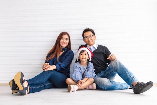 Feliz natal e boas festas! pai alegre e sua filha bonitinha sorrindo e sentado no chão.