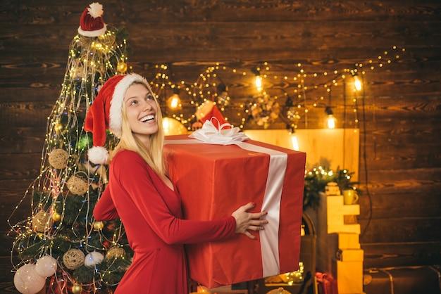 Feliz natal e boas festas, retrato de uma bela mulher sorridente com vestido de natal olhando ...