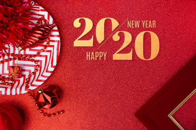 Feliz natal e feliz ano novo 2020 na vista superior vermelha de enfeites, caixa de presente, bola, fita na mesa