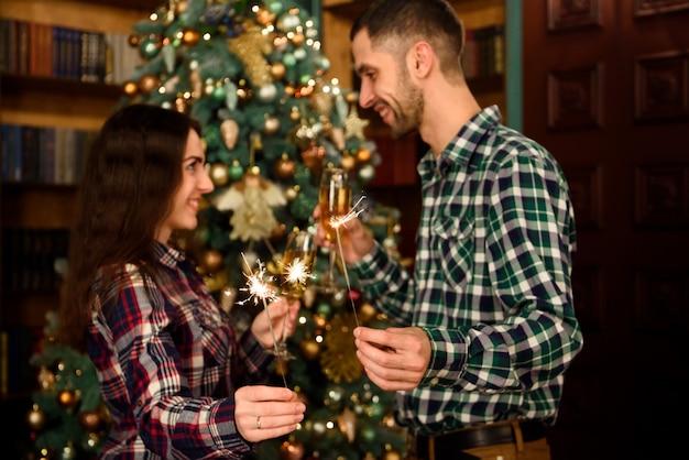 Feliz natal e feliz ano novo! casal jovem atraente está comemorando férias em casa juntos, bebendo champanhe e sorrindo com as luzes de bengala na mão