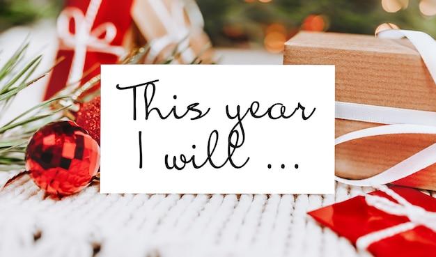 Feliz natal e feliz ano novo conceito com caixas de presente e cartão com texto este ano eu vou ...