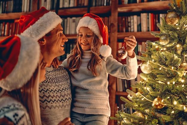 Feliz natal e feliz ano novo! família feliz comemorando o feriado de inverno em casa. mãe, pai e filha decorando a árvore do ano novo.