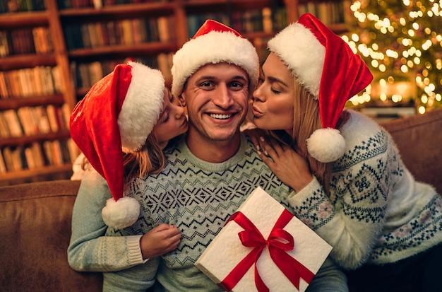 Feliz natal e feliz ano novo! família feliz está esperando o ano novo com chapéus de papai noel. mãe e filha apresentando caixa de presente para o pai.