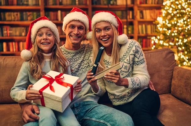 Feliz natal e feliz ano novo! família feliz está esperando o ano novo em chapéus de papai noel trocar presentes uns com os outros.