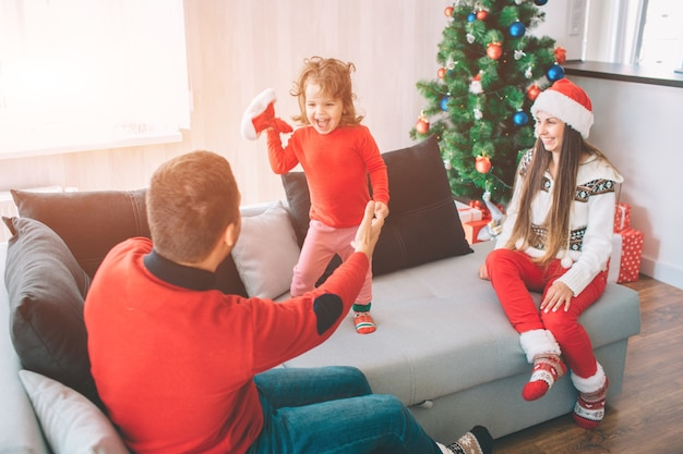 Feliz natal e feliz ano novo. foto lúdica de criança feliz em pé no sofá e segurando o chapéu vermelho. ela olha para o pai e grita. jovem pai segura a mão de sua filha. .