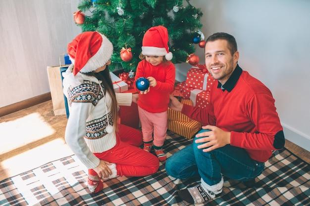 Feliz natal e feliz ano novo. homem positivo parece na câmera e sorri. ele senta-se além de menina e mulher jovem. eles estão concentrados no brinquedo de natal azul. as meninas usam chapéus vermelhos. eles estão no cobertor