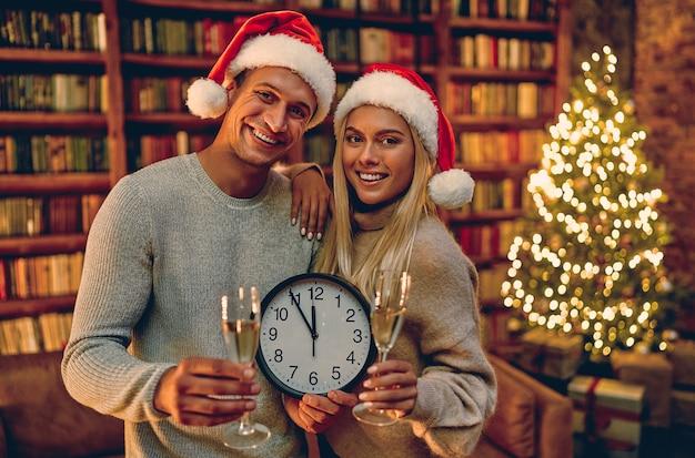 Feliz natal e feliz ano novo! jovem casal com relógio em suas mãos sorrindo cinco minutos até o ano novo. Foto Premium