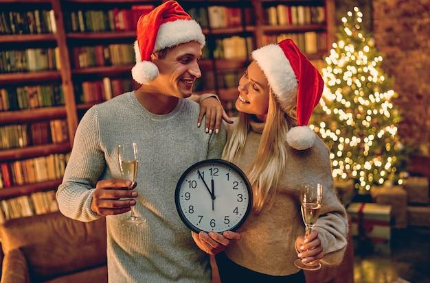 Feliz natal e feliz ano novo! jovem casal com relógio em suas mãos sorrindo cinco minutos até o ano novo.