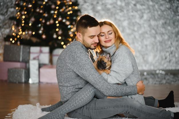 Feliz natal e feliz ano novo. jovem casal lindo está brincando com seu cachorro na sala de estar festiva de ano novo, pouco antes do natal.
