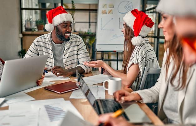 Feliz natal e feliz ano novo! jovens criativos multirraciais estão celebrando o feriado em um escritório moderno. grupo de jovens empresários está sentado em gorros no último dia útil.