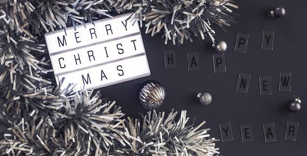 Feliz natal e feliz ano novo lightbox na mesa preta