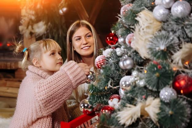Feliz natal e feliz ano novo, mãe e filha decoram a árvore de natal dentro de casa