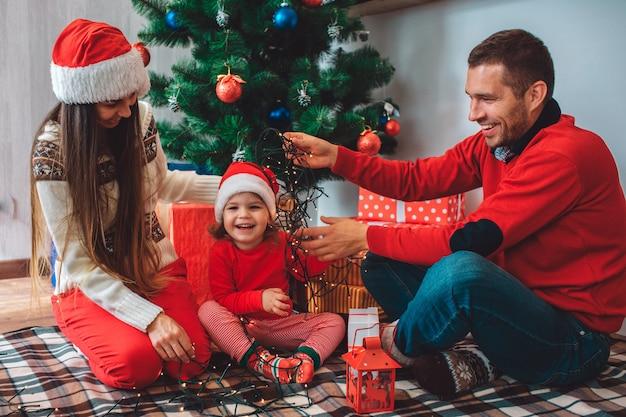 Feliz natal e feliz ano novo. menina pequena feliz senta-se entre os pais e rindo. mãe olha para baixo. ela usa chapéu. cara de suéter vermelho sorri e mantém a luz de natal em cima da cabeça da menina.