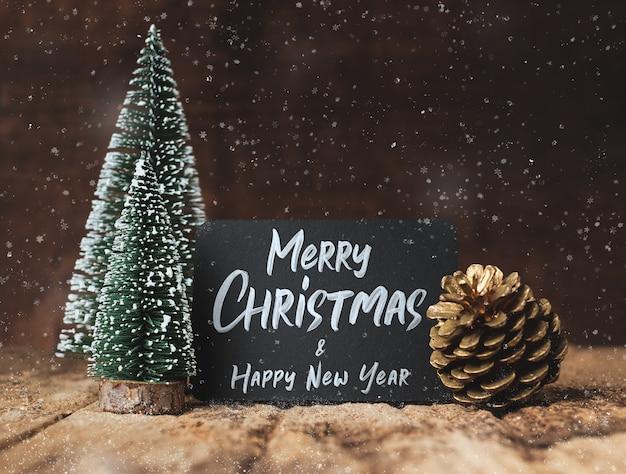 Feliz natal e feliz ano novo no quadro-negro com árvore de natal e pinha de ouro